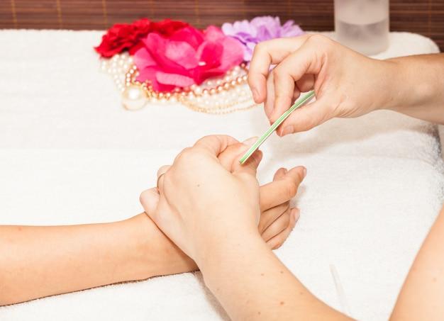 美容師は、ネイルポリッシュを入れる前に、クライアントのネイルを磨きます。