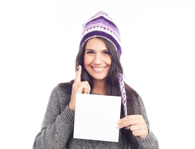 セーターとペルーの帽子のウールの看板を持っている若い女性の肖像画。白色の背景 。孤立した