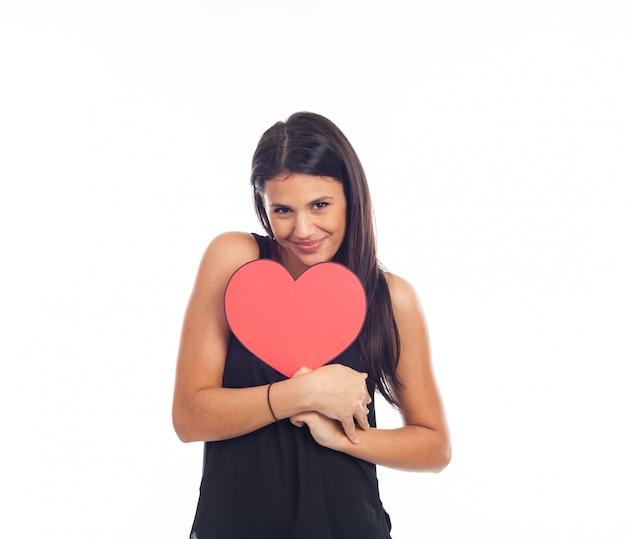 バレンタインの日に大きな赤いハートを持っている美しい幸せな若い女