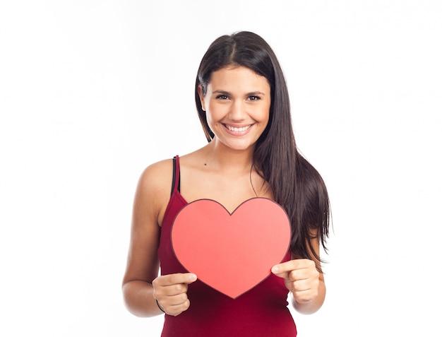 美しい幸せなブルネットの女性を保持していると大きな赤いハートを表示