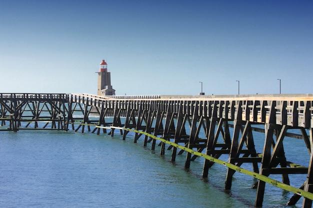 ノルマンディーフランスのフェカンプ港の木製の桟橋と灯台