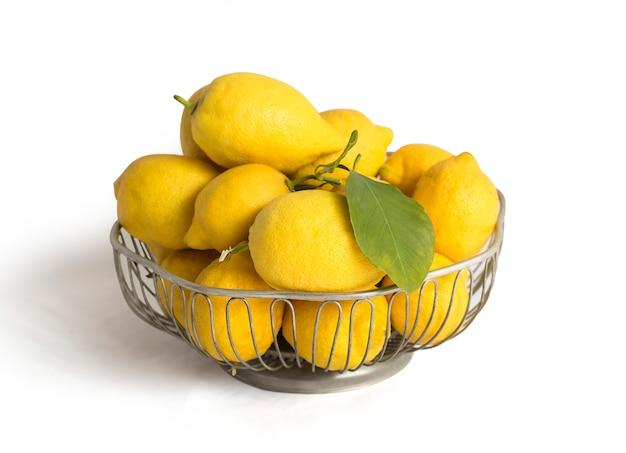 Лимоны в металлической корзине на белом фоне