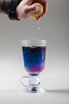 アイルランドのガラスのタイの青い蝶エンドウ豆茶..手はレモンスライスを絞ります。青茶あんちゃん、