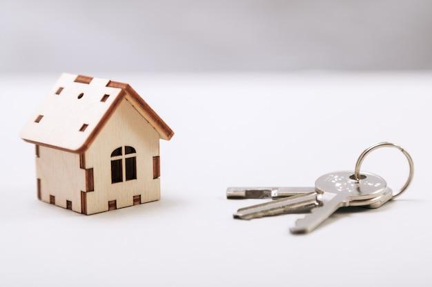 ドアの鍵を持つ木造のミニチュアの家をクローズアップ。不動産の概念コピースペースを持つキーを持つ小さなおもちゃの木造住宅