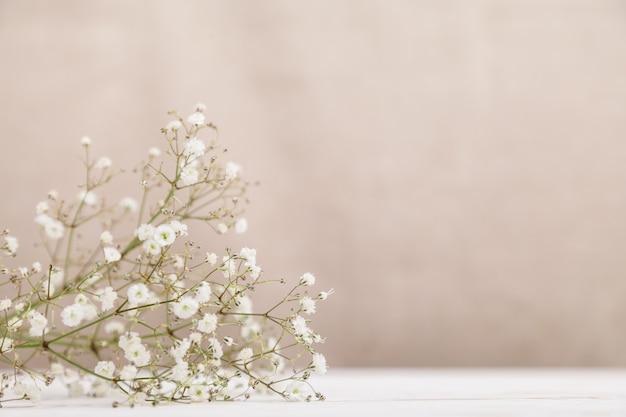 木のテーブルに小さな白い花の石膏。最小限のライフスタイルのコンセプトです。コピースペース
