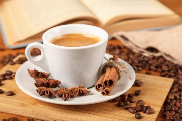 焙煎コーヒー豆のに囲まれたコーヒーエスプレッソの白いカップ