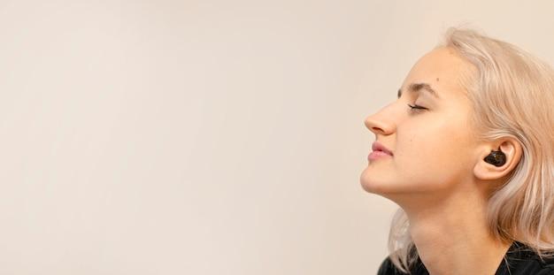 Женщина наслаждается музыкой в беспроводных наушниках. современные технологии.