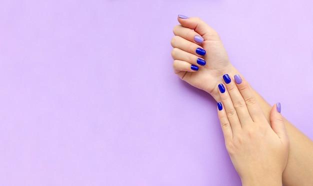 女性の手に青とライラックのマニキュア