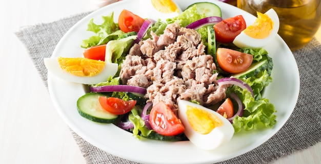 トマト、ルッコラ、マグロ、卵、ルッコラ、クラッカー、スパイスなどの新鮮な魚のツナサラダ。