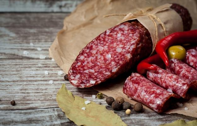 Итальянская салями с оливками и специями на деревянном фоне