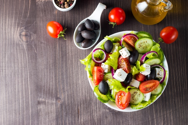 Свежий греческий салат на деревянных фоне.