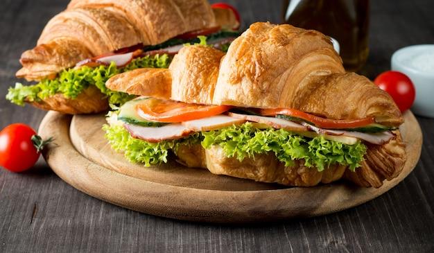 焼きたてのクロワッサンやサンドイッチサラダ、木製の背景にハム。