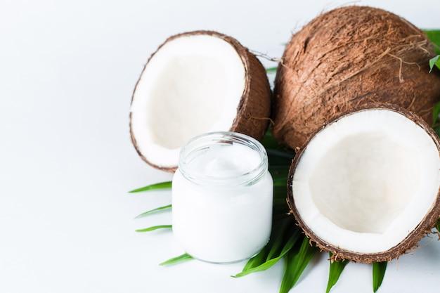 白い背景の上の緑の葉とココナッツ。