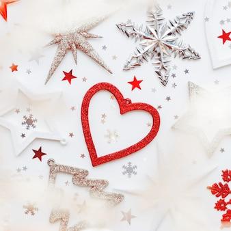 Рождество и новый год с сверкающей елкой, сердечком, снежинками и звездным конфетти. праздничные символы на белом с лампочками.