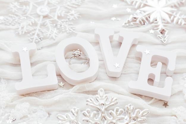 婚約ダイヤモンドリングと白い布の背景に愛」という言葉