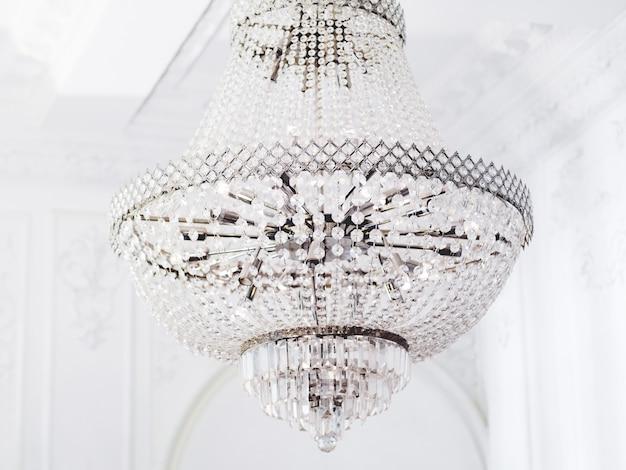 Большая многоярусная люстра со стеклянными подвесками. элемент интерьера с хрустальными деталями в белой комнате.