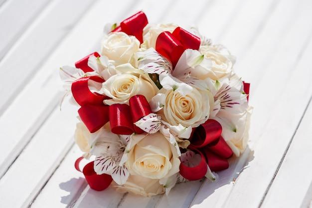 赤いリボン、ベージュのバラ、蘭の花のブライダルブーケ。