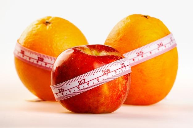 Апельсины и яблоко с линейкой портного. фруктовая здоровая витаминная диета помогает похудеть.