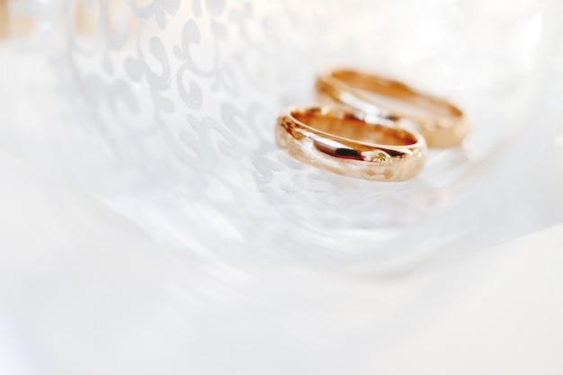 透明なガラスのウェディングゴールデンリング。愛と結婚の象徴。ガラスが日光の下できらめくクリエイティブな絵。