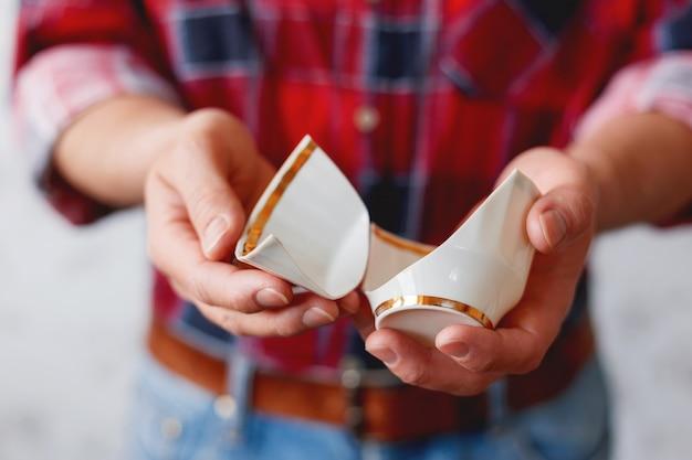 タータンチェック柄のシャツを着た男は、壊れた白いカップを保持しています。