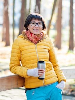 魔法瓶マグカップを保持している明るい黄色のジャケットの幸せな広い笑顔の女性。涼しい秋の日の熱いお茶。