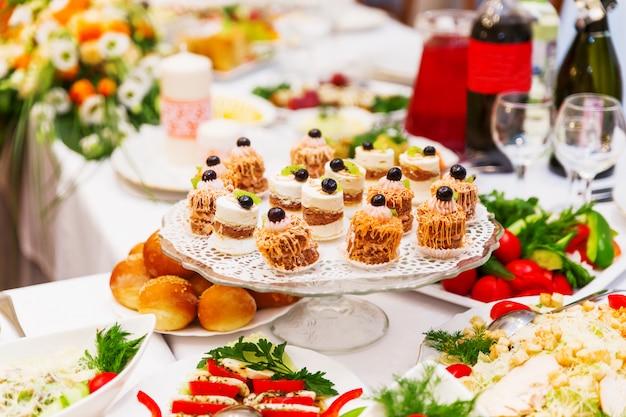 オレンジ色の結婚式の宴会用のテーブルセット。サラダ、前菜、ワイングラス。