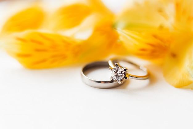 黄色のアルストロメリアの花と結婚式と婚約指輪のペア。