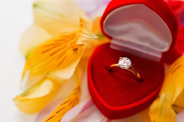 花びらの山の上の赤いギフトボックスに婚約ダイヤモンドリング。愛と結婚の象徴。