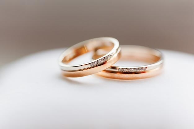 白い背景の上のダイヤモンドと黄金の結婚指輪。愛と結婚の象徴。