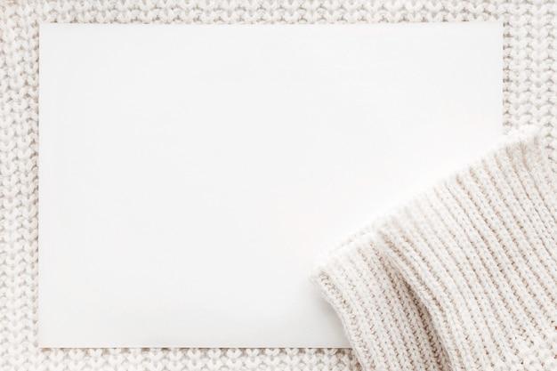 明確な紙と抽象的なニットの背景。袖付きの白いウールセーター。