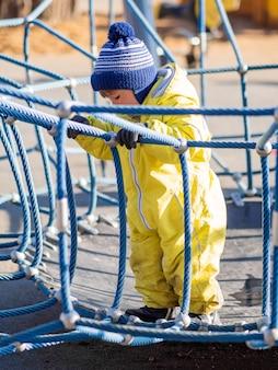 黄色のジャンプスーツの幼児男の子が子供の遊び場で遊んでいます。屋外の明るい服の子供。晴れた秋の日