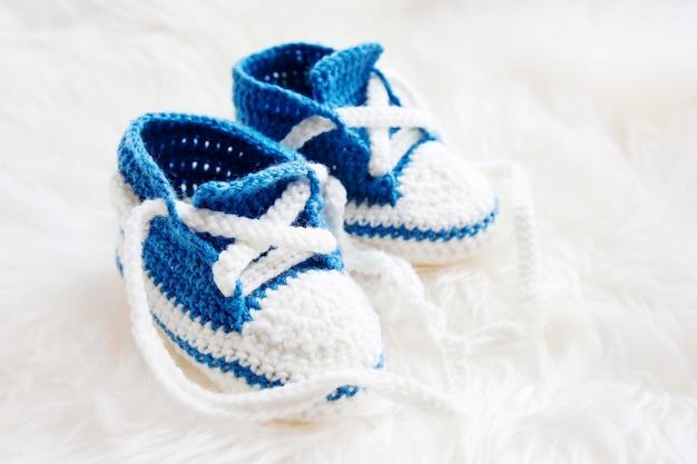 小さなベビーシューズ。生まれたばかりの少年や少女のための最初のスニーカー。かぎ針編みの手作りブーティ