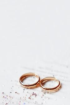 光沢のあるラインストーンの紙の招待状に黄金の結婚指輪。結婚式の詳細、愛と結婚の象徴。