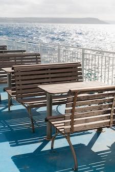 フェリーの上部デッキにある木製のテーブルとベンチ。