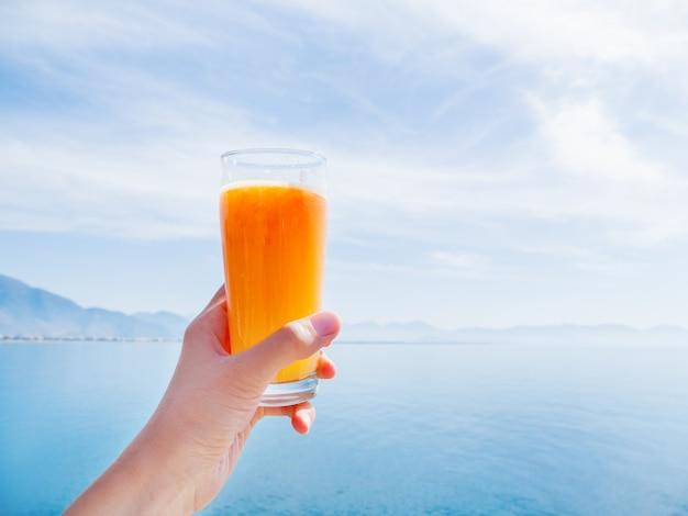 ガラスに熟したオレンジの新鮮でおいしい絞りたてのジュースを手にします。