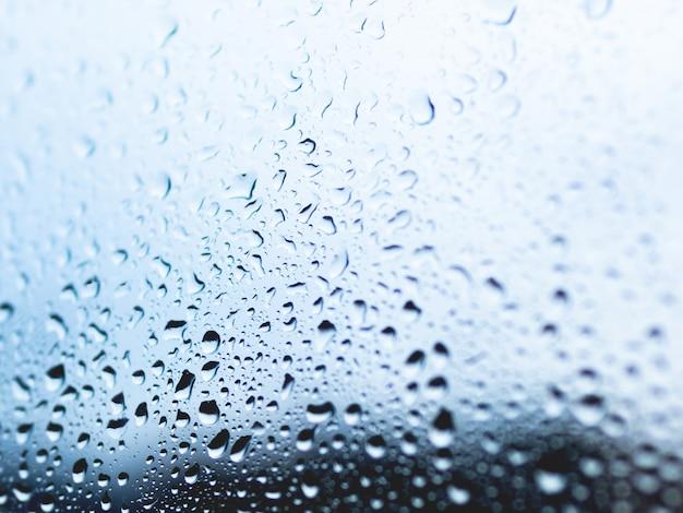 Капли дождя на фоне стекла. силуэты капель воды на синей прозрачной поверхности.