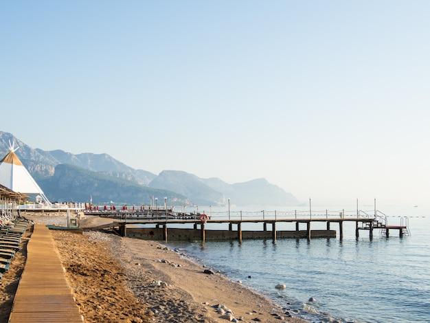 ビーチで早朝。サンラウンジャーと木製のポンツーンを備えた典型的なトルコのホテル。ケメル、トルコ。