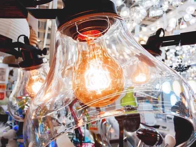 透明なガラスプラフォンと昔ながらの電球を備えたシャンデリア。グローアーフィラメントとヴィンテージの電球。白熱、レトロなデザイン。
