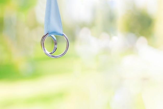 黄金の結婚指輪と光の青いリボンのダイヤモンドのペア