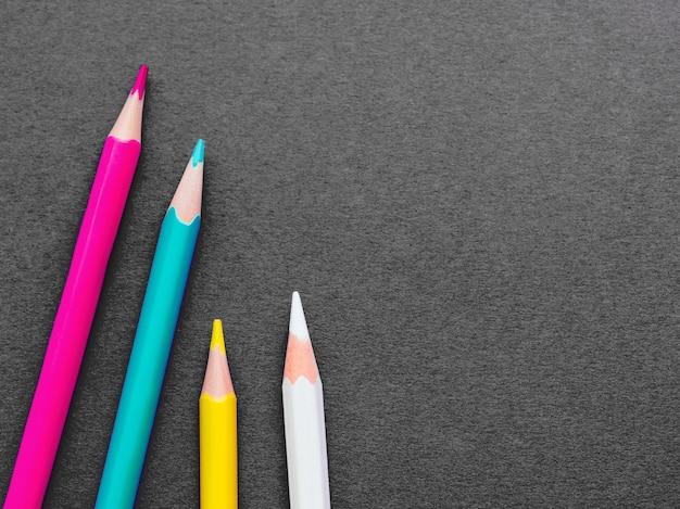 暗い灰色の紙の背景にカラフルな水彩鉛筆の行。学用品