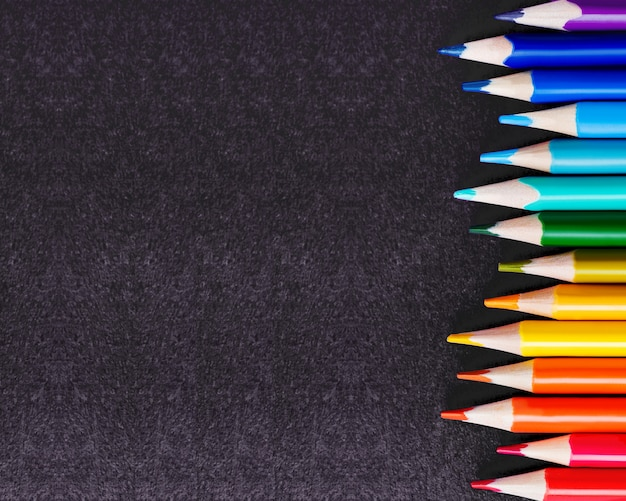 黒の背景にカラフルな水彩鉛筆の行。学用品