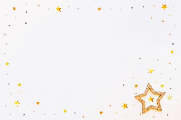 輝く黄金の星のフレームと紙吹雪