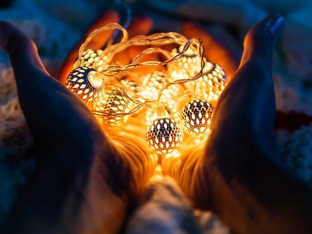 装飾的な電球でいっぱいの手