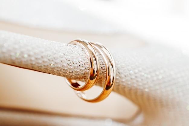 ラインストーンの花嫁の靴の黄金の結婚指輪。ウェディングジュエリーの詳細。愛と結婚の象徴。