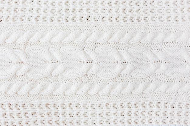 ニットの抽象的な背景。ウールの白いセーターのテクスチャ。