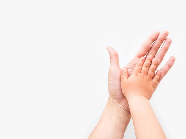 大人と子供の手。母親と子供は手のひらを合わせます。
