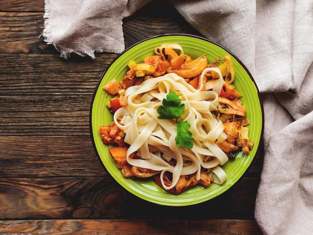 おいしいフェットチーネボロネーゼとトマトソースのグリーンプレート。木製のテーブル、ナプキン、パスタボウルのトップビュー。イタリア料理。