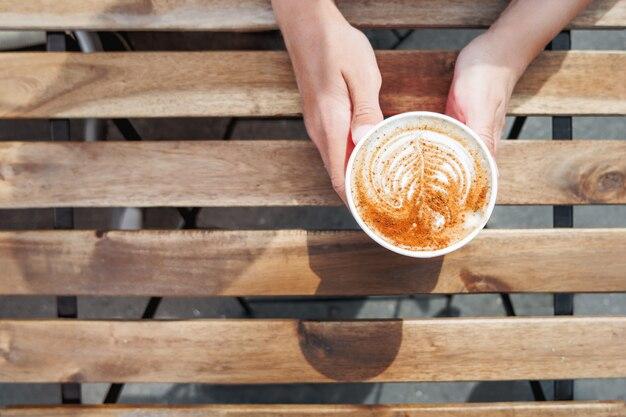 Женщина, держащая бумажный стаканчик с кофе. кофе с собой. вкусный горячий напиток на деревянный стол в солнечный день. еда на свежем воздухе. плоская планировка, вид сверху.