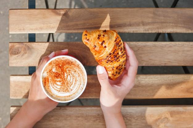 Женщина, держащая бумажный стаканчик с кофе и шоколадным круассаном