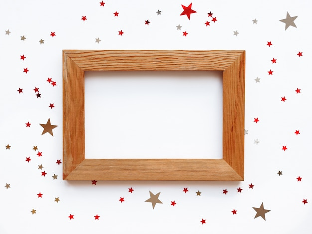Потертая деревянная фоторамка на белом фоне с рассеивающим звездным конфетти
